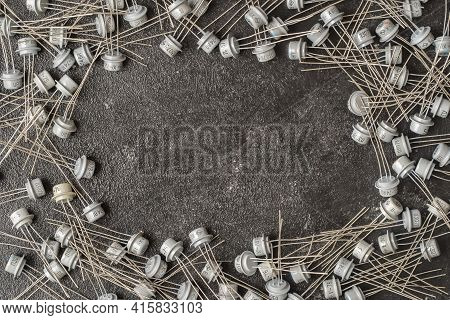 Old Many Soviet Transistors In Metal Case On Black Background With Copy Space For Your Text. Electro