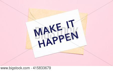 On A Light Pink Background - A Craft Envelope. It Has A White Sheet Of Paper That Says Make It Happe