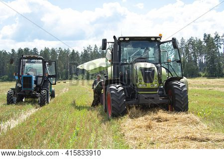 A Blue Tractor And A Green Claas Tractor Remove Straw On The Field. One Tractor Broke Down And It Is