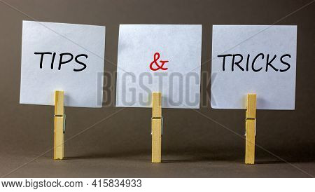 Tips And Tricks Symbol. White Papers On Wooden Clothespins. Words 'tips And Tricks'. Beautiful Grey