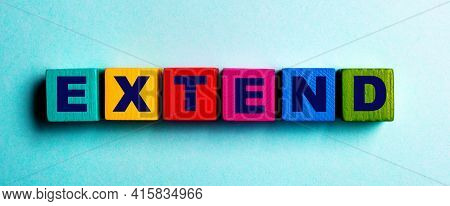 The Word Extend Is Written On Multicolored Bright Wooden Cubes On A Light Blue Background