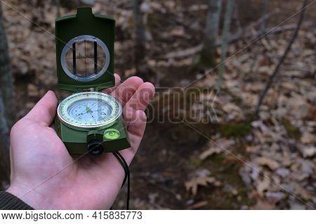 A Hand Is Holding A Prismatic Compass And Raising It For Navigational Use On A Hiking Trail In This