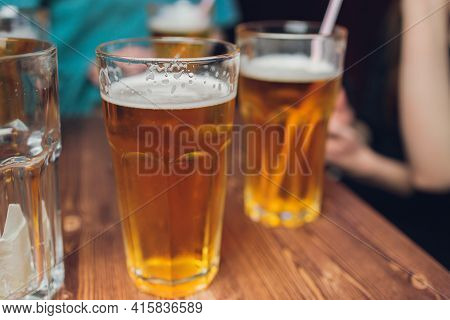 Four Friends With A Fresh Beer In A Beer Garden Close-up On Beer Stein.