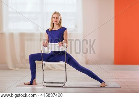 Beautiful Blonde Woman In Blue Sportswear, Practicing Yoga, Performs A Warrior Pose On A Chair To Re