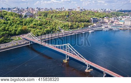 Aerial Top View Of Kiev City From Above, Kyiv Skyline, Hills, Pedestrian Park Bridge And Dnieper Riv
