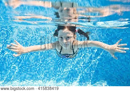 Little Child Swims Underwater In Swimming Pool, Happy Active Girl Dives And Has Fun Under Water, Kid