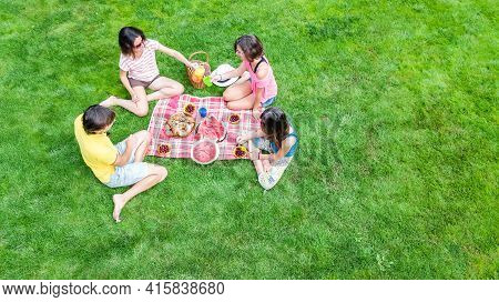 Happy Family With Children Having Picnic In Park, Parents With Kids Sitting On Garden Grass And Eati