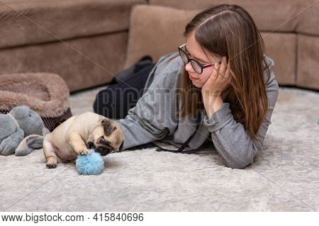 A Girl With Long Hair In Glasses Lies On A Light Carpet And Plays With A Pug Puppy. The Pug Puppy Pl