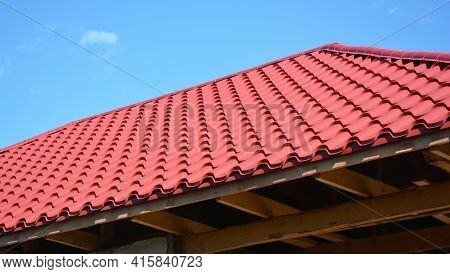 A Close-up Of An Unfinished Metal Roof With Red Metal Roofing Tiles, Wood Ceiling Joists, Eaves, And