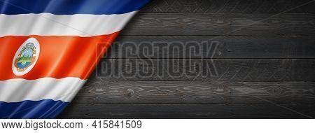 Costa Rica Flag On Black Wood Wall. Horizontal Panoramic Banner. 3d Illustration