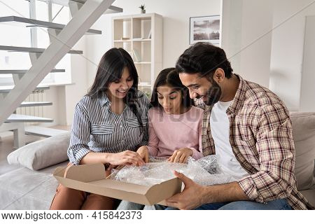 Excited Indian Family With Child Daughter Unpack Parcel At Home. Happy Parents And Teen Kid Daughter