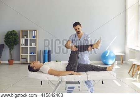 Man Professional Doctor Osteopath In Uniform Moving Up And Checking Man Patients Legs Joints