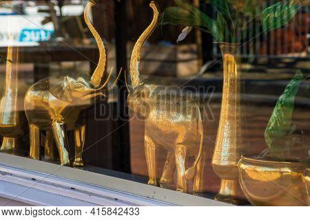 Yellow Metal Elephant Figures In The Store Window
