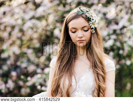 Natural Beauty Young Woman With Long Hair Walks In The Summer Garden, Enjoying The Blooming Spring N