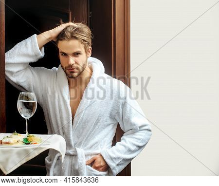 Man In Hotel. Young Handsome Man In White Terry Bathrobe In Hotel Near Human Hand Of Waiter With Foo