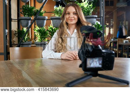 Portrait Of Young Smiling Woman With Beautiful Long Hair Sitting At Table And Giving An Interview In