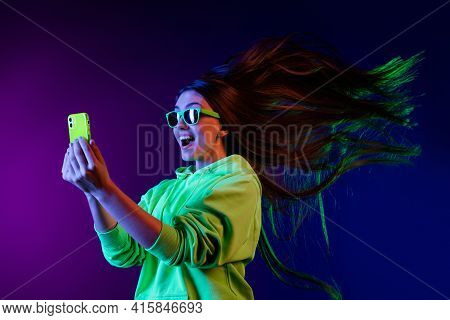 Photo Of Amazed Shocked Young Woman Look Phone Fast Internet Fly Hair Isolated On Colorful Neon Back