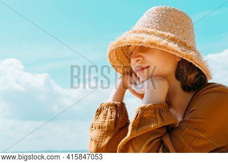 Portrait Of Beautiful Woman Wearing Straw Hat. Closeup Face Of Romantic Girl Enjoying Summer.