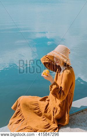 Young Woman In Beautiful Dress Sits On The Pier By The Lake And Enjoys Nice Nature View. Portrait Of