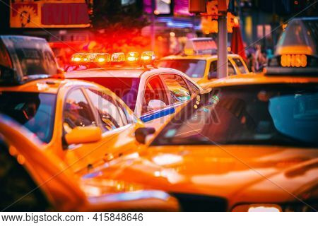 New York City Police patrol car flashing beacon siren lights in busy NYC traffic jam with yellow taxi cabs cars. Urban background.