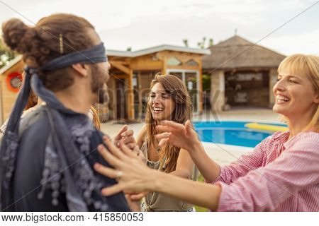 Group Of Cheerful Young Friends Having Fun At Poolside Summertime Outdoor Party, Playing Blind Man's