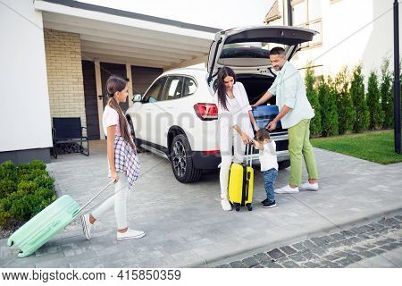 Full Size Photo Of Optimistic Cute Family Pack Baggage In Car Wear Casual Cloth Near Home Outdoors