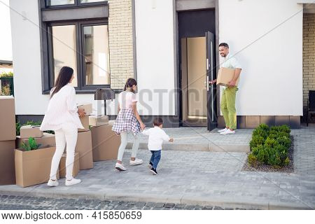 Full Body Portrait Of Lady Cheerful Man Open Door Small Kids Running Carton Boxes Near House Outdoor