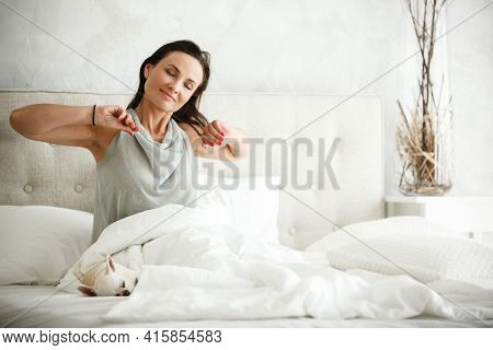 Lazy morning concept. Beautiful happy woman wakes up in bed and streches hands. Attractive female resting at home in bedroom. Little dog sleeps near on white sheets