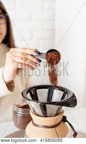 Young Woman Brewing Coffee In Coffee Pot Sitting At The White Table With Various Stuff For Alternati