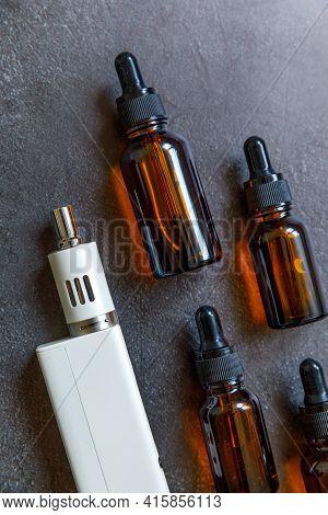 Vaping Device E-cigarette Electronic Cigarette And Liquid Bottles On Dark Black Stone Shale Backgrou