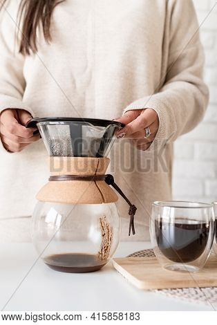 Young Woman Brewing Coffee In Coffee Pot And Cutting A Cake