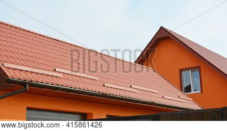 Metal Roofing Construction: A Red Metal Gable Roof With Snow Stoppers, Snow Guards And Roof Gutters