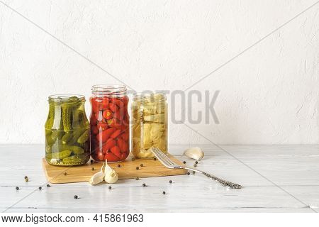 Open Glass Jars With Canned Vegetables On A White Wooden Table. Artichoke In Oil, Pickled Gherkins A
