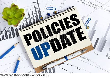 Policies Update. Text On White Notepad Paper On A Light Background Near Financial Charts