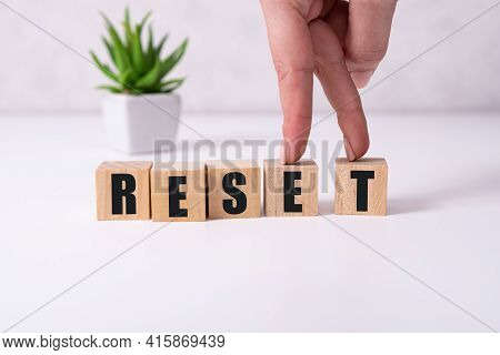 The Hand Puts A Wooden Cube With The Letter R From The Word Reset. The Word Is Written On Wooden Cub