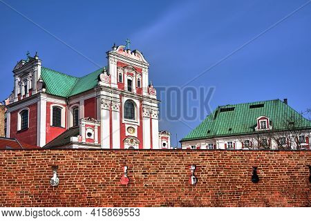 A Medieval, Historic Defensive Wall And A Baroque Church Façade In Poznan