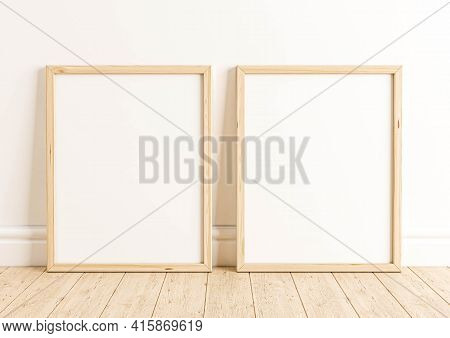Double 8x10 Vertical Wooden Frame Mockup On Wooden Floor And White Wall. Two Empty Poster Frame Mock