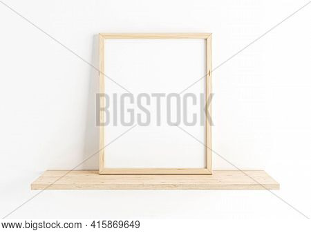 Single 8x10 Vertical Wooden Frame Mockup On Wooden Shelf And White Wall. One Empty Poster Frame Mock