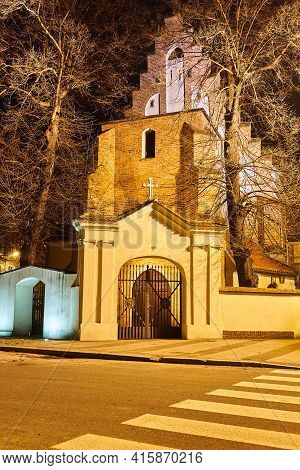 The Gate And The Facade Of A Gothic, Historic Church During The Night In Poznan