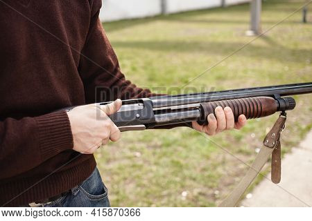 A Man Charges A Pump-action Shotgun With A Ammo. 12 Caliber. Tyre Outdoor. A Man In Headphones And G