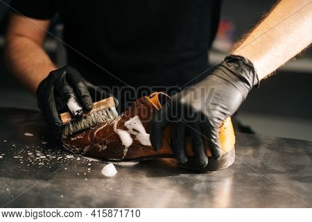 Close-up Hands Of Unrecognizable Shoemaker In Black Gloves Applying Cleaning Foam On Old Light Brown