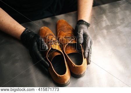 Close-up Top View Of Hands Of Shoemaker Shoemaker In Black Gloves Holding Old Worn Light Brown Leath
