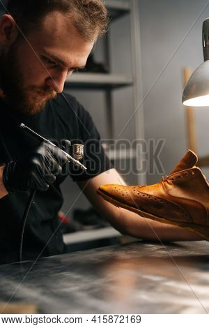 Portrait Of Bearded Shoemaker Wearing Black Gloves Spraying Paint Of Light Brown Leather Shoes, Clos
