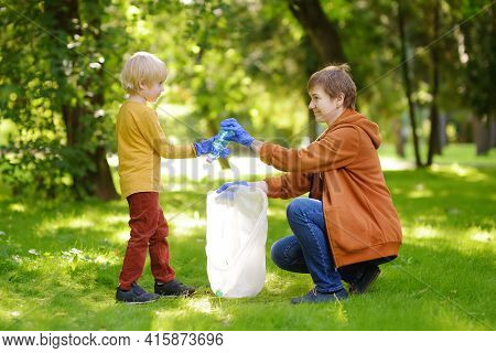 Woman Volunteer And Little Boy Picking Up The Plastic Garbage And Putting It In Biodegradable Trash-