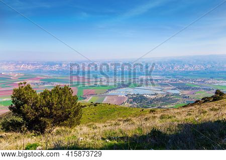 Jezreel Valley in the Lower Galilee. Warm winter in Israel.  Picturesque agricultural fields cover the entire valley
