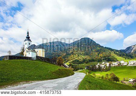 White bell tower and church on a hill near the small village. Green grassy  lawns in mountain valley. Travel to Slovenia. Picturesque Julian Alps