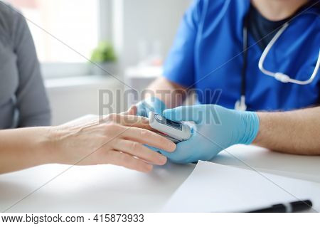 A Woman At A Doctor's Appointment During The Coronavirus Epidemic. Doctor Checking Oxygenation With