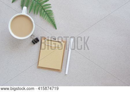 Craft Notebook, Note Paper, Pen, Coffee Cup And Fern Leaf On Beige Background, Workplace Concept, Pl