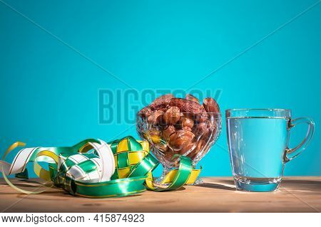 Muslim Iftar Of Breaking Of Fast During Ramadan Month With Preserved Sweet Dates And Water. Ketupat