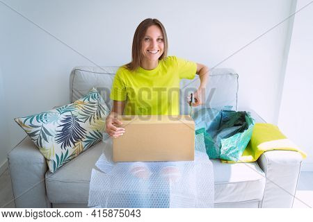 Young Woman Opens Cardboard Box Or Parcel Package From Online Store. Happy Satisfied Customer Unboxi